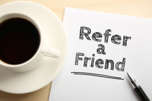 44577748 - text refer a friend written on the white paper with pen and a cup of coffee aside.